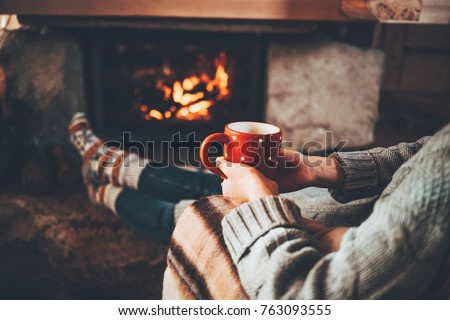 Feet in woollen socks by the Christmas fireplace. Woman relaxes by warm fire with a cup of hot drink and warming up her feet in woollen socks. Cozy atmosphere. Winter and Christmas holidays concept. #763093555