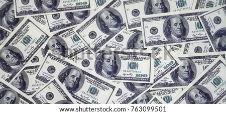 A pile of one hundred US banknotes with president portraits. Cash of hundred dollar bills, dollar background image with high resolution Royalty-Free Stock Photo #763099501