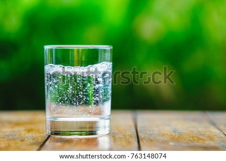 A glass of water on green background. The wooden table. Pure water with gas. Sparkling water Royalty-Free Stock Photo #763148074