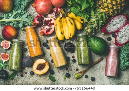 Flat-lay of colorful smoothies in bottles with fresh tropical fruit and superfoods on concrete background, top view. Healthy, clean eating, vegan, vegetarian, detox, dieting breakfast food concept #763166440