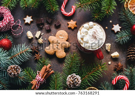 Hot chocolate with marshmallows, gingerbread cookies, spices and candy cane. Christmas sweets. Winter holidays food, table top view