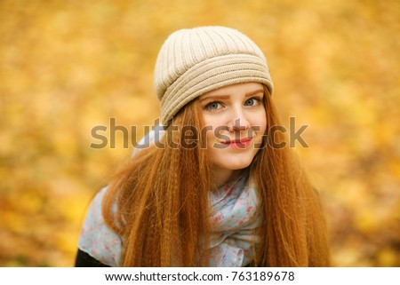Portrait of a beautiful red-haired girl with a kind face in a light hat looking at the camera against a background of yellow autumn foliage during a walk in the city park. European woman #763189678