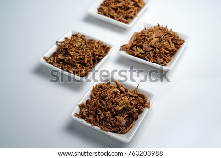 Malaysian Onion fries (Bawang Goreng) on white plate with isolated white background #763203988
