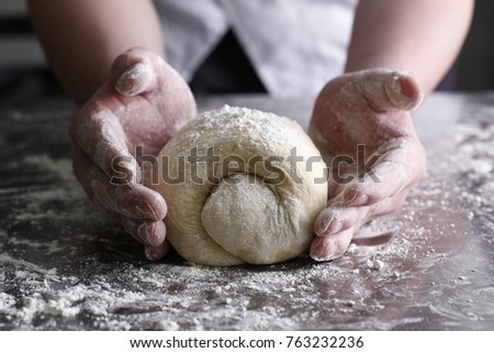 Men male female mom grandma mother hands sprinkle kneading a bread pie wheat dough with flour close up on a messy metal table in the kitchen, dough will rise before baking in oven #763232236