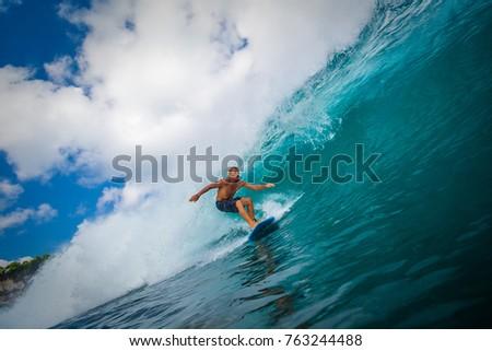Indonesia, Bali, July 22 2016: A surfer riding big overhead blue ocean wave #763244488