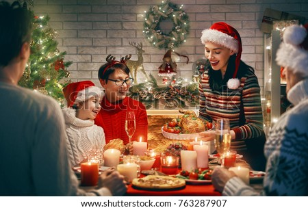Merry Christmas! Happy family are having dinner at home. Celebration holiday and togetherness near tree. Royalty-Free Stock Photo #763287907