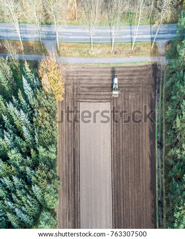 Vertically aligned aerial photograph taken with the drone of an area of arable land treated by a tractor #763307500