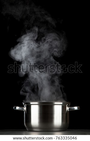 Steaming pot on black background Royalty-Free Stock Photo #763335046