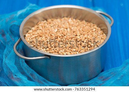 uncooked spelt in pot on wooden background #763351294