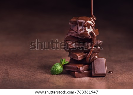 melted chocolate pouring into a piece of chocolate bars with green mint leaf on a table #763361947
