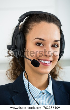 Young woman call center operator talking with client by headset #763386109