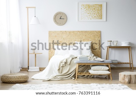 Paper clock and gold painting on the wall above bed with beige bedsheets in bedroom with pouf and wooden furniture #763391116