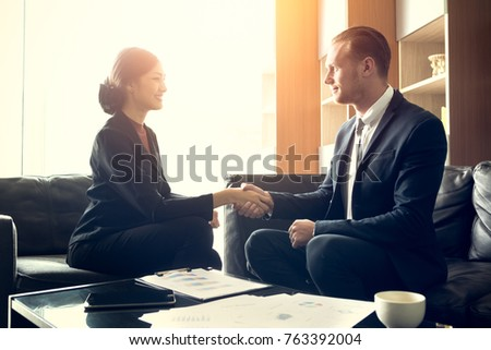 Buseness meeting and successful concept - two smiling businessman and businesswoman shaking hands after they have good deal in executive room at modern office, startup business project plan concept #763392004