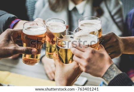 Group of friends enjoying a beer in brewery pub - Young people hands cheering at bar restaurant - Friendship and youth concept - Warm vintage filter - Main focus on bottom hand Royalty-Free Stock Photo #763401241
