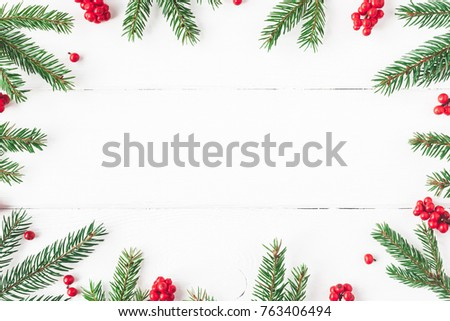 Christmas composition. Christmas frame made of fir tree branches and red berries on white background. Flat lay, top view, copy space #763406494