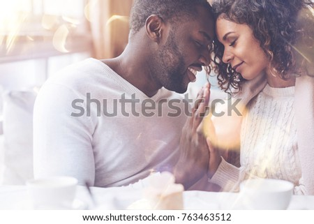 Tender mood. Young loving couple sitting opposite each other smiling and closing their eyes, holding hands together #763463512