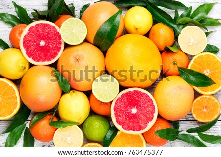 Citrus fruits background. Assorted fresh citrus fruits with leaves. Orange, grapefruit, lemon, lime, tangerine. Top view #763475377
