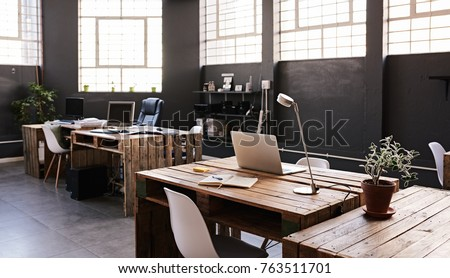Modern office space with tables and chairs, computers and office supplies with no employees  #763511701