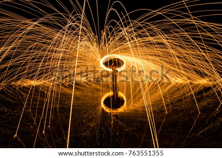 Long exposure image of steel wool photography, light painting in the night at the lake. Soft focus due to long exposure