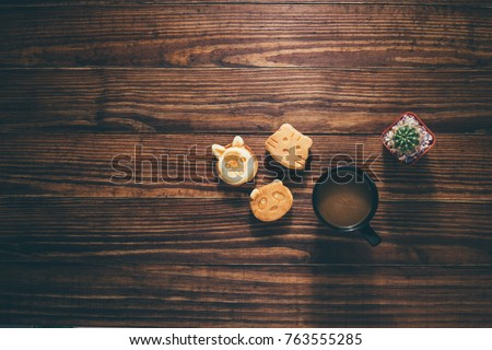 The breakfast coffee on dark wooden background, candy, coffee, cactus on wooden, with copy space, Working desk table concept. #763555285