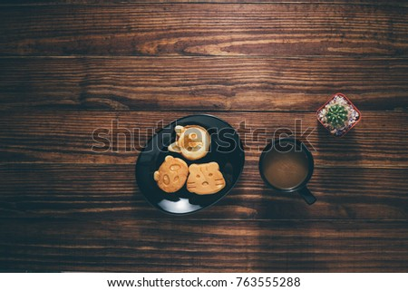 The breakfast coffee on dark wooden background, candy, coffee, cactus on wooden, with copy space, Working desk table concept. #763555288