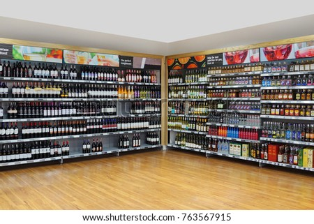 PENANG, MALAYSIA - NOVEMBER 16, 2017: An assortment of wine and hard liquor bottles stacked neatly on store shelves in a local supermarket, Penang, Malaysia #763567915