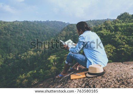 Asian man travel relax in the holiday. seats relax read books on rocky cliffs. On the Moutain. In Thailand #763580185
