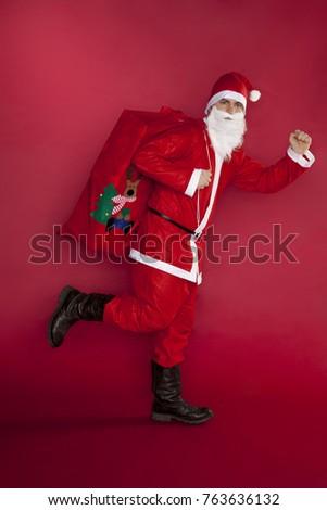 Santa Claus runs with gifts bag #763636132