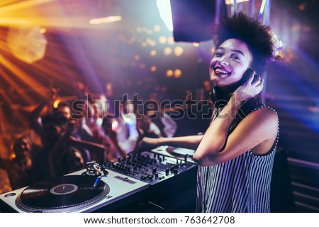 Shot of a female DJ playing music at a nightcub Royalty-Free Stock Photo #763642708