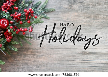 Happy Holidays Text with Christmas Evergreen Branches and Berries in Corner Over Rustic Wooden Background #763681591