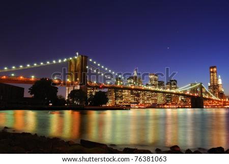 The Brooklyn Bridge illuminate at night with skyscrapers behind. #76381063
