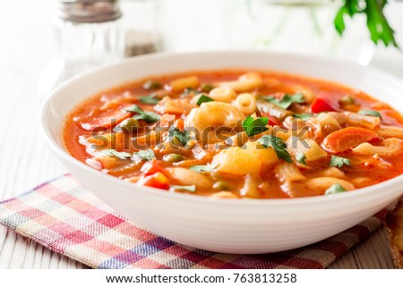 Italian minestrone soup on white wooden background. Selective focus. #763813258