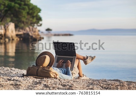 Young woman using laptop computer on a beach. Girl freelancer working by a sea. Freelance work, travel, vacations, stay connected, communication, studying online, e-learning concept Royalty-Free Stock Photo #763815154