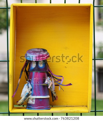 Colorful plastic creature in a yellow wooden box #763821208