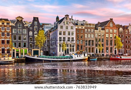 Bridge over channel in Amsterdam Netherlands houses river Amstel landmark old european city spring landscape #763833949