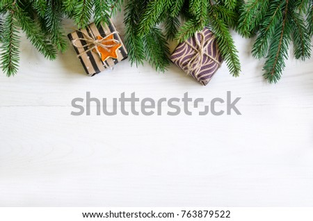 Christmas still life with gifts on a white wooden background with a Christmas tree. New Year gifts #763879522
