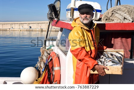 fisherman with a fish box inside a fishing boat Royalty-Free Stock Photo #763887229