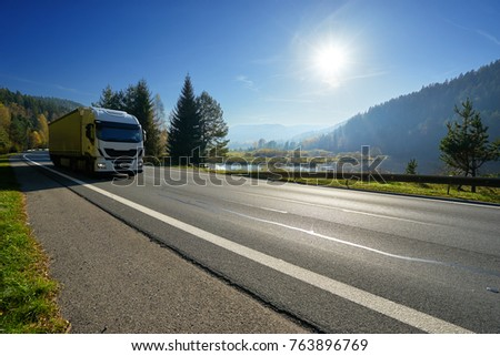 Glowing sun over the valley. White truck driving on the road around a lake and forested mountains in autumn. #763896769
