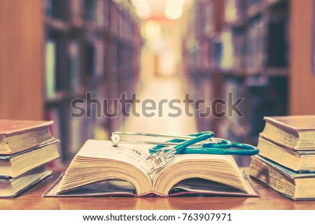 Old book in library with stethoscope on open textbook, stack piles of texts on reading desk, and aisle of bookshelves in  study class room background for medical school education learning concept #763907971