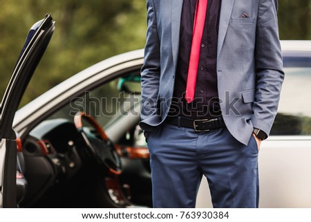 Successful businessman in a dark business suit with a red tie against the background of a car. Stylish man. Fashionable watch on hand. Hand in pocket #763930384