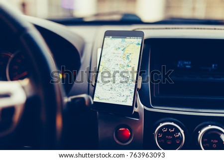 The map on the phone in the background of the dashboard. Black mobile phone with map gps navigation fixed in the mounting. Vintage style photo #763963093