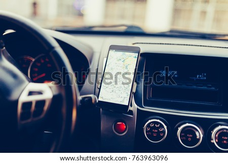 The map on the phone in the background of the dashboard. Black mobile phone with map gps navigation fixed in the mounting. Vintage style photo #763963096