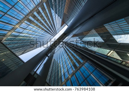 Bottom view of modern skyscrapers in business district against blue sky #763984108