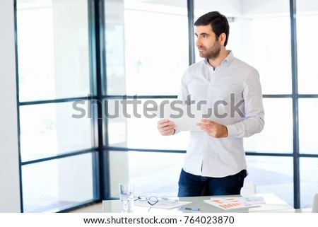 Young caucasian businessman standing in office #764023870