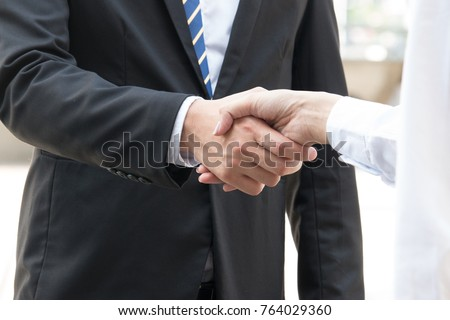 Businessman is shaking hand with woman , focus at hand.shake hands, When you shake hands with somebody, you must look him in the eye. shake hands,  #764029360