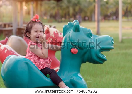 Cute little curly hair asian baby girl enjoy riding kids toy horse outdoors in the garden at sunset light. Babyhood and childhood activity concept.