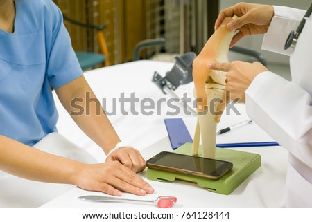 Professional doctor are recommending female patients for knee treatment. medical concept. #764128444