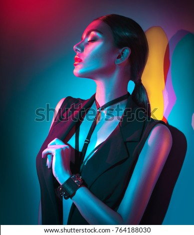 Sexy young woman portrait, on colorful background. Seductive brunette model girl in black sexy clothes, fashion accessories, bright makeup in neon light. Clubber, night life #764188030