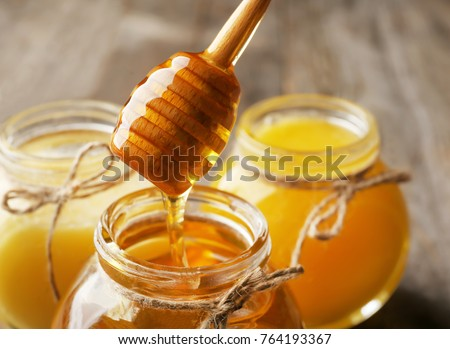 Pouring aromatic honey into jar, closeup #764193367