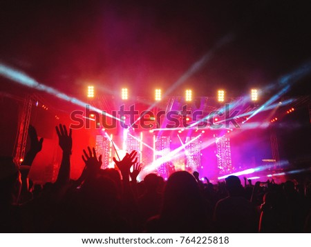 Music concerts, people are raising their hands in black and colorful lights. #764225818